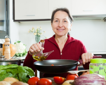 Happy mature woman pouring oil into  skillet at kitchen photo