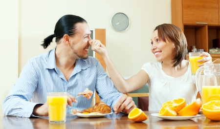 bacon portrait:  Happy couple laughing in breakfast time at home Stock Photo