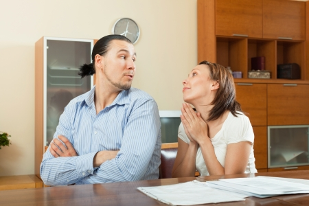 parsimony: Smiling woman asking for money from  husband for the purchase at home