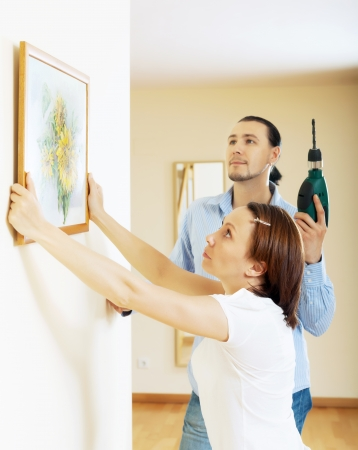 serious middle-aged couple choosing place for picture in frame on the wall at home interior photo
