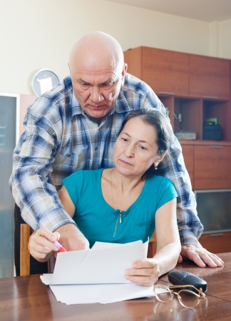 fills: Mature woman fills documents, man helps her