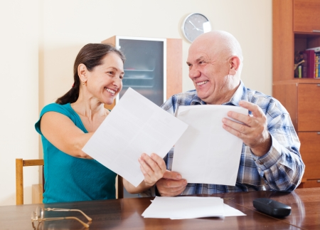 parsimony: Happy senior couple holding financial documents at home