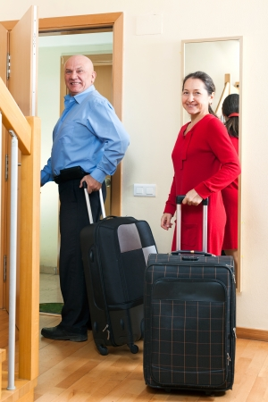 positive mature couple with luggage in home going on vacation photo