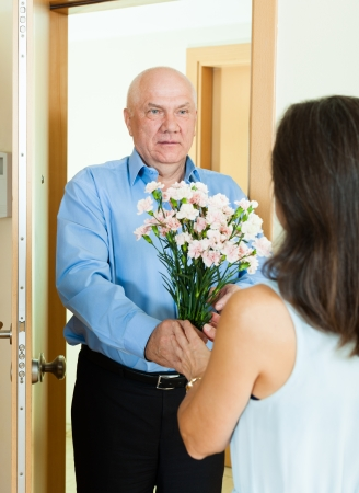 Mature man giving bunch of flowers to  woman at home door photo