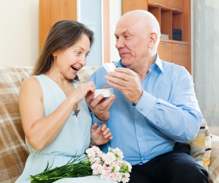 Mature man presenting surprised woman jewel in box  photo