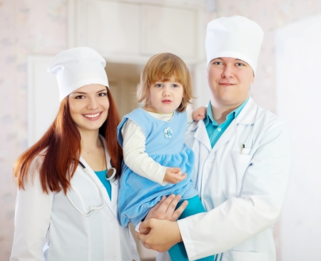 Portrait of doctor and nurse with child at medical clinic photo