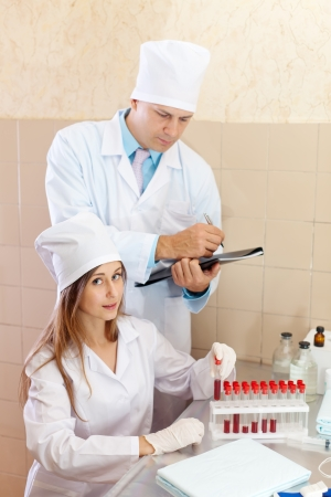 Male doctor and nurse with test tubes makes blood test in medical laboratory photo