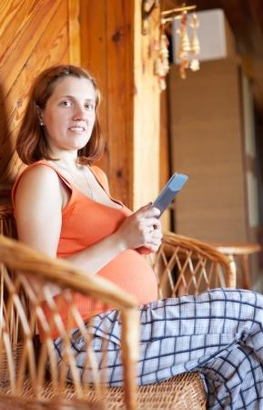 pregnant woman reads e-book in home interior photo
