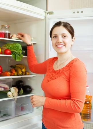 refrigerator kitchen: Smiling woman near refrigerator at domestic kitchen