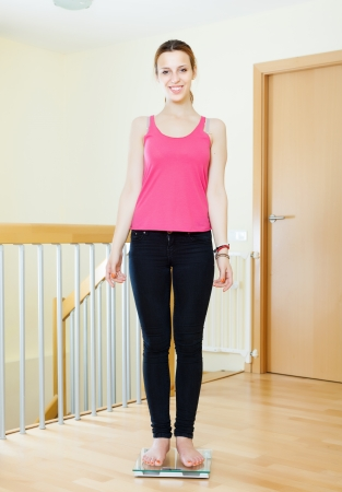 bathroom scale: cheerful girl standing on bathroom scales at home interior