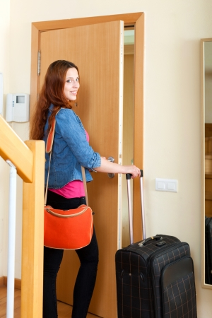 Happy red-haired woman with big luggage locking door and leaving her home  photo