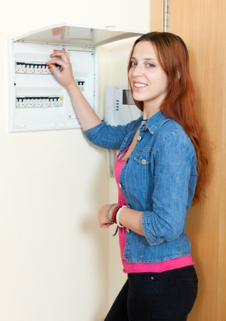 Woman near power control panel  at home  photo