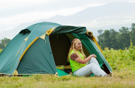 Happy female tourist in front camp tent photo