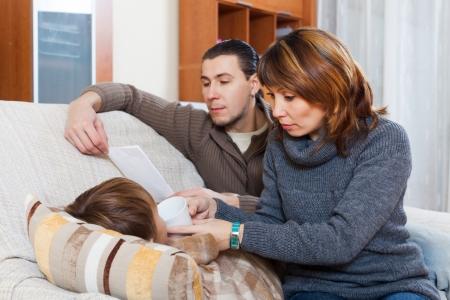 medicament: Los padres que dan medicamento l�quido con el hijo enfermo en casa Foto de archivo