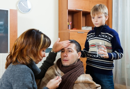 nosotrophy: Ailing man surrounded by caring wife and son at home Stock Photo