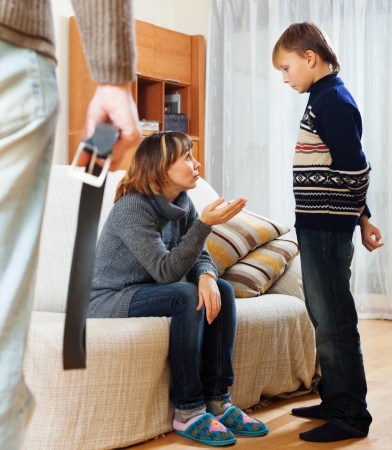 Mother and father with belt scolding teenager son at living room photo