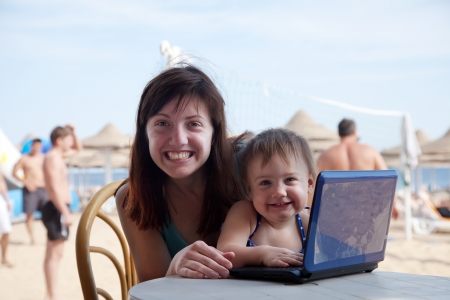 resort beach: happy mother and  toddler  sitting  with laptop at resort beach