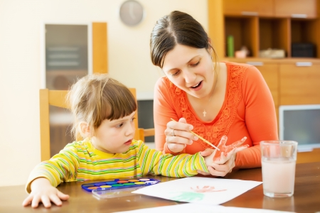 handbreadth: Happy mother and baby  plays with watercolor in home