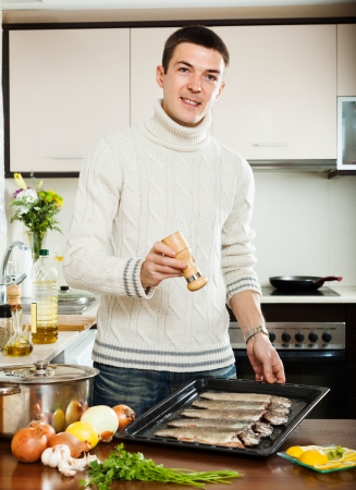 roasting pan: Handsome man adding spices in raw fish on roasting pan at home kitchen