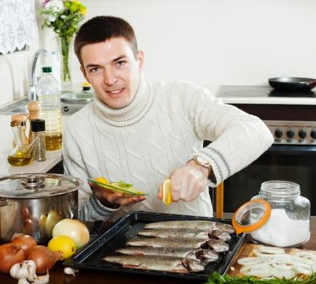 roasting pan: Handsome guy cooking raw fish with lemon in roasting pan