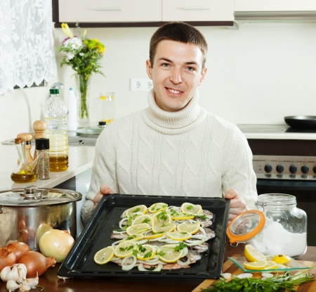 cheeful:  man with raw fish on roasting pan at home kitchen