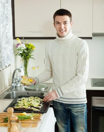 roasting pan: Handsome man with fish on roasting pan