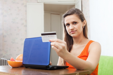 woman paying by credit card in internet store at home  photo