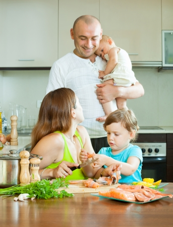20 23 years: Happy parents with children cooking  fish at home kitchen Stock Photo