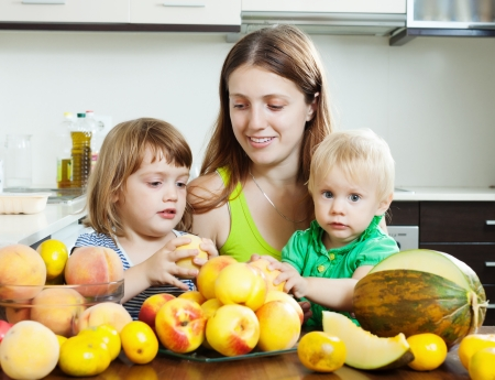 ordinary woman: Ordinary woman with two daughters eating melon and peaches