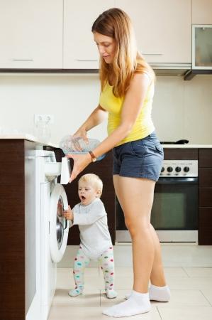 Happy woman  and child putting whitener in to washing machine