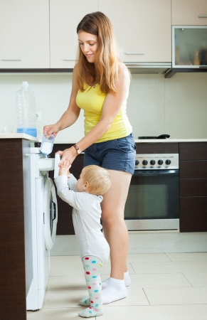 Happy long-haired woman  and child putting whitener in to washing machine