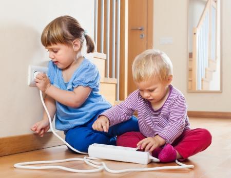 집에서 바닥에 전기를 가지고 노는 두 아이 스톡 콘텐츠