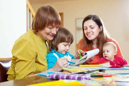 Senior woman with daughter and grandchildren drawing on paper at home. Focus on mature photo