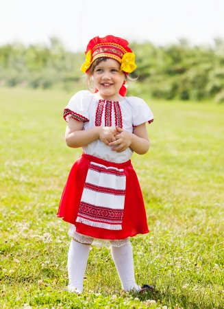 child in russian folk clothes on grass photo