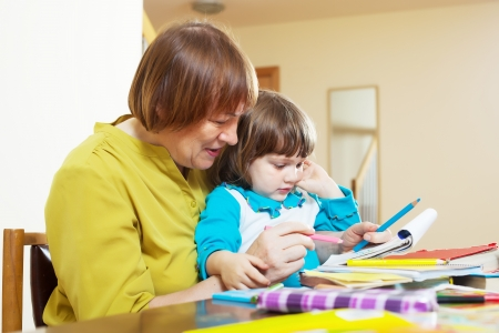 Mature woman and child sketching  on paper at table in home interior Stock Photo - 24864996