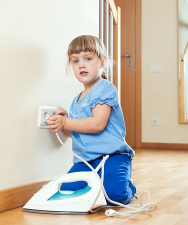 girl  playing with electric iron at home photo