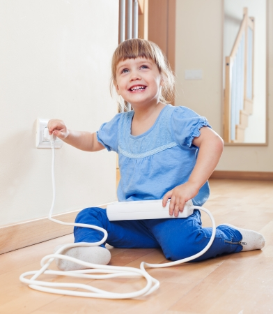 Happy three year old child playing with electricity at home Imagens