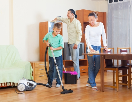 Ordinary family of three doing housework together in home photo