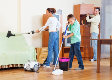 casua: Ordinary family of three with teenager doing housework with  cleaning equipment in living room Stock Photo