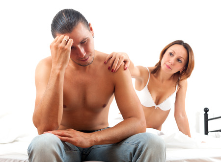 Sad middle-aged man has problem, a wife comforting him in bed at bedroom