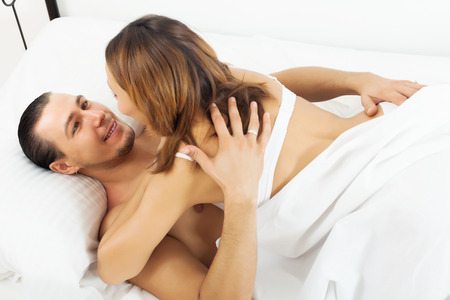 Man and woman having sex on white sheet in bed  photo