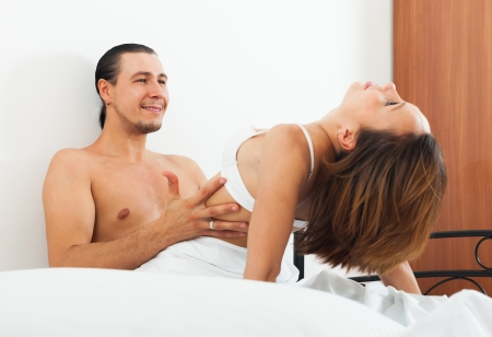 Ordinary couple having sex on bed in home interior photo