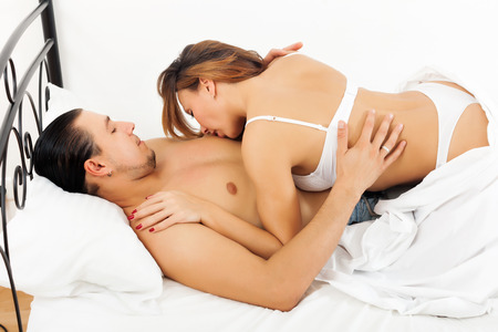 woman kissing her man in chest in bed   photo