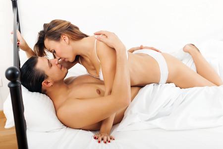 sexo cama: chico y chica teniendo sexo en la hoja blanca en la cama