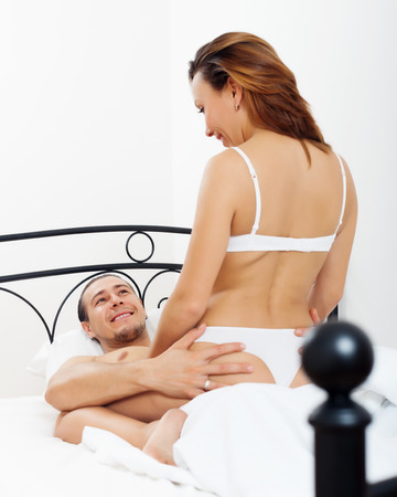Handsome man playing with woman in bed photo