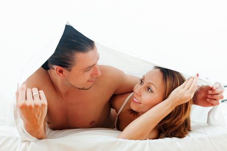 Portrait of  couple  together under sheet   photo