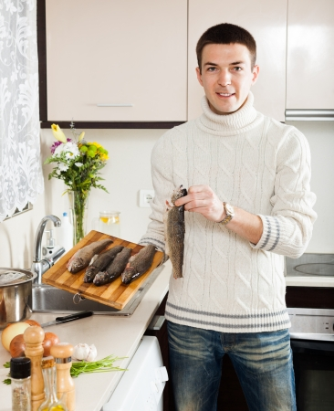Handsome man holding raw trout  at home kitchen  photo