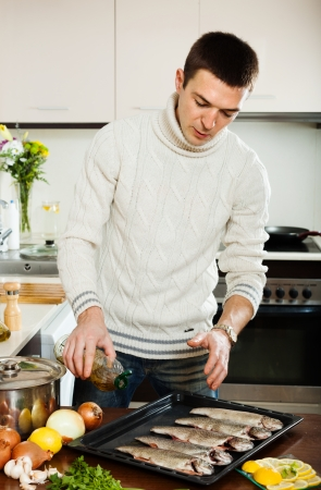 brook trout: Handsome man pouring oil in raw fish on roasting pan