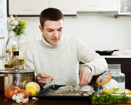 roasting pan: man cooking raw fish with onion in roasting pan