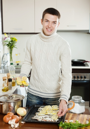 fryingpan: Handsome man cooking raw fish with lemon and onion in baking sheet at home kitchen  Stock Photo
